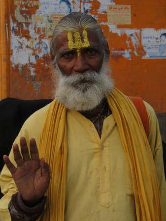 varanasi: VARANASI, INDIA - NOV 6, 2009 - Hindu Sadhu gives blessings on the bathing ghats of Varanasi on 6 Nov 2009in Varanasi, India. Editorial