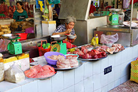 city fish market: SAIGON - FEB 5, 2015 - Woman eating late breakfast at her stall in the fish market Saigon (Ho Chi Minh City),  Vietnam