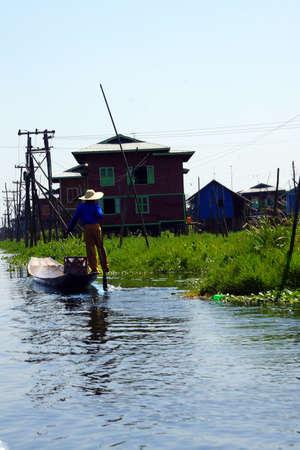 脚ローイング漁師は、インレー湖で, ミャンマー (ビルマ) の彼の小さいボートを推進します。 写真素材