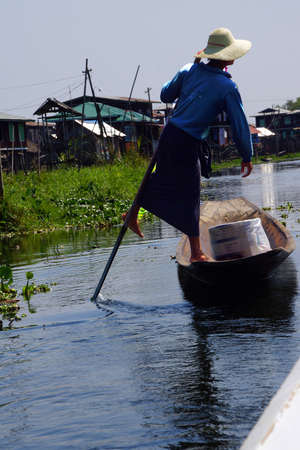 脚ローイング漁師は、インレー湖で, ミャンマー (ビルマ) の彼の小さいボートを推進します。 写真素材 - 55704451