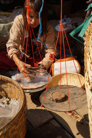 weekly market: INLE LAKE, MYANMAR - MAR 1, 2015 - Young woman sells fresh fish at the weekly market on  Inle Lake,  Myanmar (Burma)