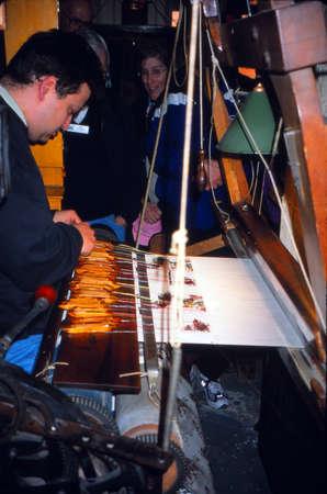 lyon: LYON, FRANCE - MAR 16, 2001 - Weaver at loom making silk brocade in Lyon, France Editorial