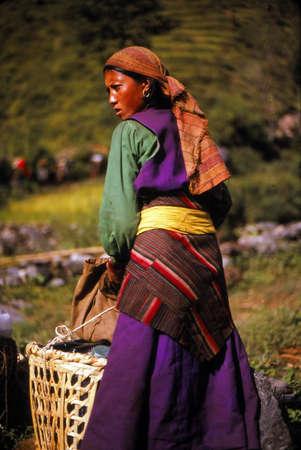 NEPAL HIMALAYAS - OCT 1, 1979 - Sherpani trekking porter resting at ridgetop Tamang village,Khumbu Himalaya,Nepal, Asia