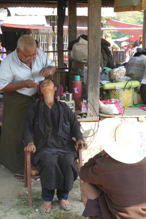weekly market: INLE LAKE, MYANMAR - MAR 1, 2015 - Dentist treats a patient at the weekly market,  Inle Lake,  Myanmar (Burma)
