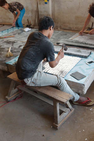 silvery: KYAUKME, MYANMAR - FEB 21, 2015 - Hammering lead sheets to make silvery lead foil,Kyaukme Myanmar (Burma) Editorial