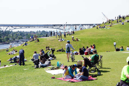 dozens: SEATTLE - MAY 30, 2016 - Dozens of people celebrate a relaxing Memorial Day at Gas Works Park