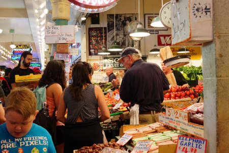 pike place market: SEATTLE - JUN 3, 2016 - Young women buy fresh fruit at the Pike Place Market