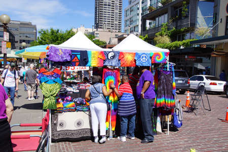 the place is outdoor: SEATTLE - JUN 3, 2016 - Buying t-shirts at an outdoor stand at the Pike Place Public Market , Seattle