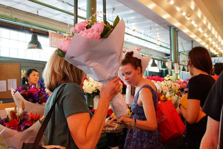 pike place: SEATTLE - JUN 3, 2016 - Young women buy bouquets  at the Pike Place Public Market , Seattle Editorial