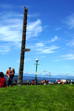 public market: SEATTLE - JUN 3, 2016 - People enjoy a sunny day under the totem pole at Pike Place Public Market Editorial