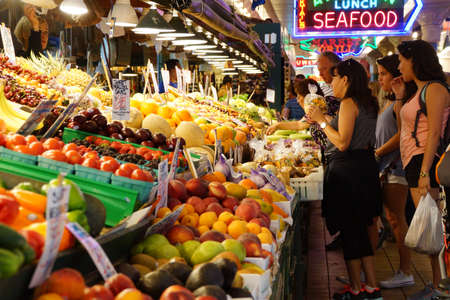 pike place: SEATTLE - JUN 3, 2016 - Young women buy fresh fruit at the Pike Place Market