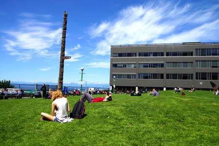 pike place: SEATTLE - JUN 3, 2016 - People enjoy a sunny day under the totem pole at Pike Place Public Market Editorial