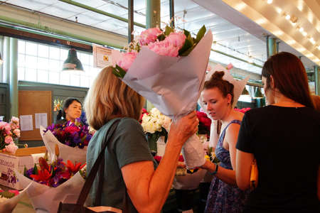 public market: SEATTLE - JUN 3, 2016 - Young women buy bouquets  at the Pike Place Public Market , Seattle Editorial