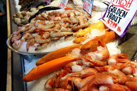 public market: SEATTLE - JUN 3, 2016 - Golden trout and other seafood on display at the Pike Place Public Market Editorial