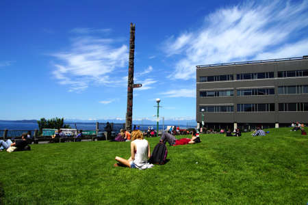 pike place market: SEATTLE - JUN 3, 2016 - People enjoy a sunny day under the totem pole at Pike Place Public Market Editorial