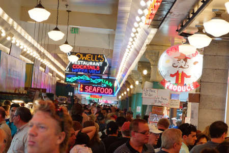 pike place market sign: SEATTLE - JUN 3, 2016 - Tourists browse the vendors stalls  at the Pike Place Public Market , Seattle