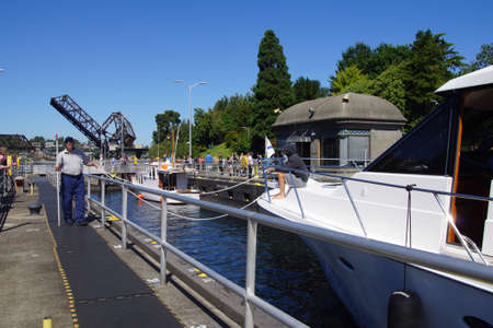 SEATTLE - JUL 24, 2016 - White yacht moves through the  the Hiram Chittenden Locks in Seattle