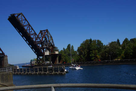 weighted: SEATTLE - JUL 24, 2016 - Pleasure boat cruises towards counter weighted railroad bridge, Seattle Editorial