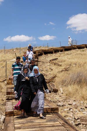 descend: GOBEKLI TEPE, TURKEY - JUN 8, 2014 - Tourists descend from visiting the archaeological site Editorial