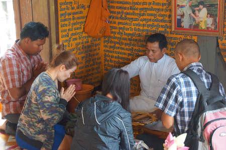 astrologer: PHNOM KULEN, CAMBODIA - FEB 15, 2015 - Buddhists consult a fortune teller astrologer at  Phnom Kulen, Cambodia