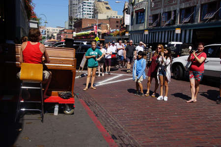 busker: SEATTLE - AUG 4, 2016 - Piano busker entertains visitors to the Pike Place Market