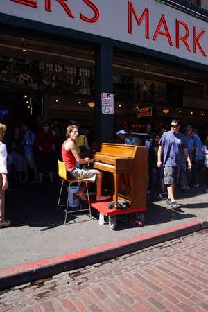 SEATTLE - 4 augustus 2016 - Piano busker entertaint bezoekers van de Pike Place Market Redactioneel