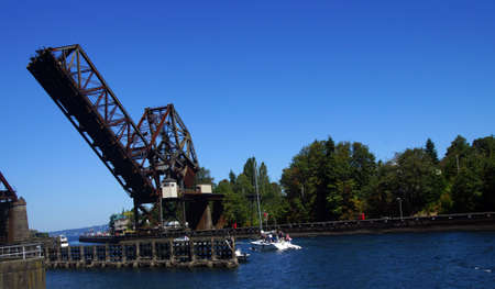 SEATTLE - JUL 24, 2016 - Pleasure boat cruises towards counter weighted railroad bridge, Seattle 新闻类图片