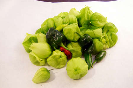 Green tomatillo and chili peppers  for salsa verde, fresh from Seattle garden isolated on white Stock Photo
