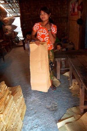 lye: KYAUKME, MYANMAR - FEB 21, 2015 - Young Shan woman stacks sheets of  bamboo paper,  Kyaukme, Myanmar (Burma) Editorial