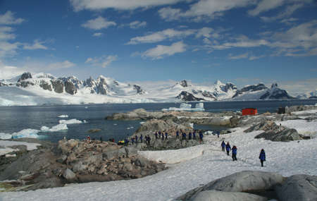 Cruise  tourists moving down to landing station, amid icebergs & glaciers  Petermann Island, Antarctica Фото со стока
