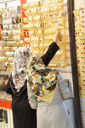 scarves: BURSA, TURKEY - MAY 22, 2014 - Women with scarves choosing golden bracelets  in the bazaar of  Bursa, Turkey