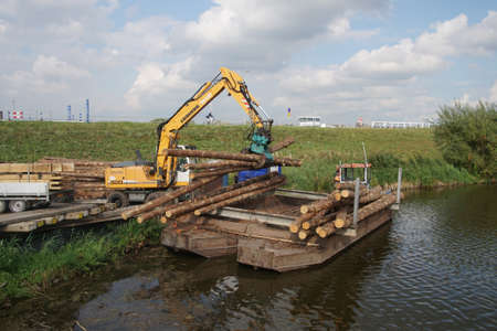 barge: KINDERDIJK, NETHERLANDS - SEP 16, 2016 - Loading logs for transport on a canal barge,  Kinderdijk, Netherlands