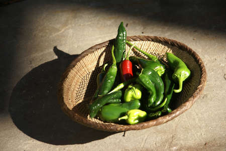 A variety of fresh green chilies in a woven basket