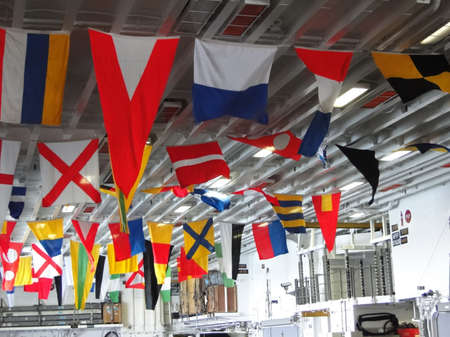 cypher: Signal flags displayed on the hangar deck  of on the hangar deck  of the Amphibious Assault Ship Bonhomme Richard, LDH-6,  on Aug 4, 2011, in Seattle. Editorial