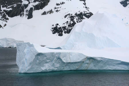 Iceberg floating offshore, overcast day,  Neko Harbor, Andvord Bay, Antarctica  版權商用圖片