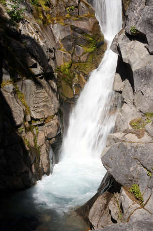 Christine falls surges through a narrow canyon  in Mount Rainier National Park Stock Photo