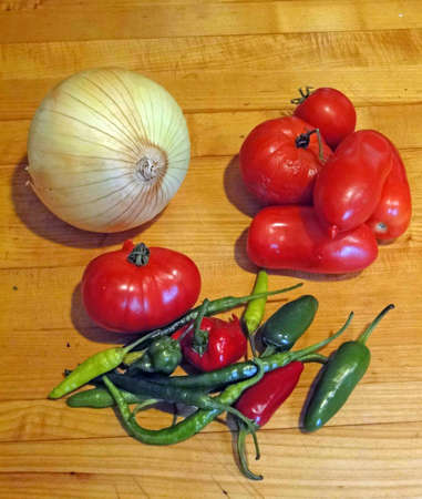 Tomatoes, onion and variety of chili peppers fresh from the garden and ready to eat