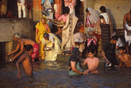 VARANASI,  INDIA  - NOV 16, 1976 - Hindu pilgrims bathe in the Ganges River at dawn, Varanasi ( Benares),  India