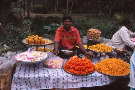 GUJARAT, INDIA - OCT 29, 2003 - Man verkoopt jalabees en andere zoetigheden op een markt in Gujarat, India