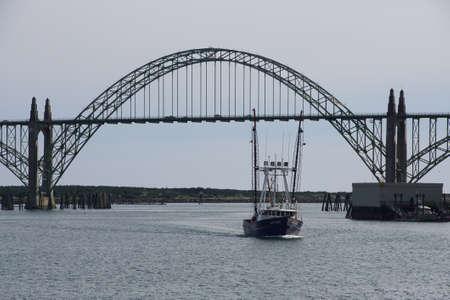 Fishing troller passes under the Yaquina Bay Bridge  to enter the harbor at  Newport, Oregon Stock Photo