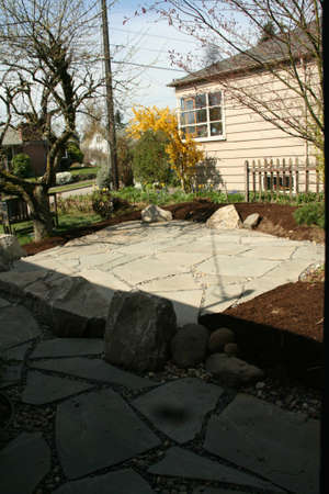 Flagstone patio before landscaping is finished, in a Seattle garden