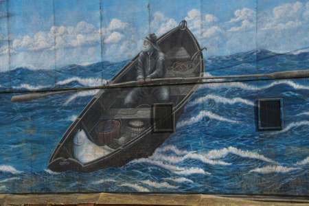 NEWPORT, OREGON - APR 22, 2017 - Outdoor wall mural of a dory fisherman,  Newport, Oregon