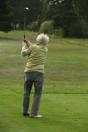 Woman golfer teeing off,Agate Beach  Newport, Oregon coast Stock Photo