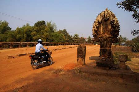 Motorcycle passes Naga serpent on ancient 8th century Angkor bridge,  near Kampong Thom,  Cambodia
