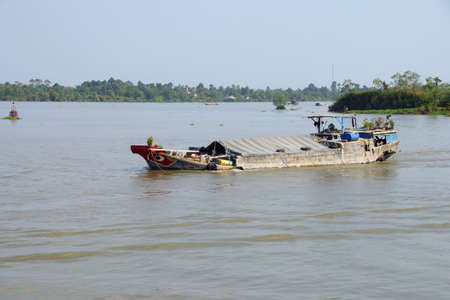 Working barges on the Mekong River,  Vietnam Stock Photo