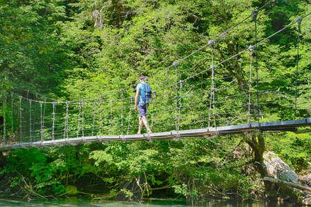 Hiker crosses the suspension bridge leading to the Grove of the patriarchs, Ohanapecosh, Mount Rainier National Park, Washington