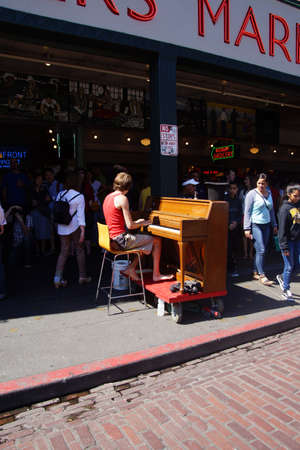 pike place: SEATTLE - AUG 4, 2016 - Piano busker entertains visitors to the Pike Place Market