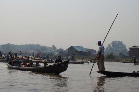 INLE LAKE, MYANMAR - FEB 28, 2015 - Large oared boat ferries local villagers across  Inle Lake,  Myanmar (Burma)
