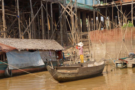 stilt: Stilt houses and boats during dry season at the Kompong Kleang floating fishing village,  Cambodia Editorial