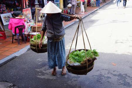 Vietnamese  woman carrying fresh vegetables and baskets,   Hoi An, Vietnam Editorial